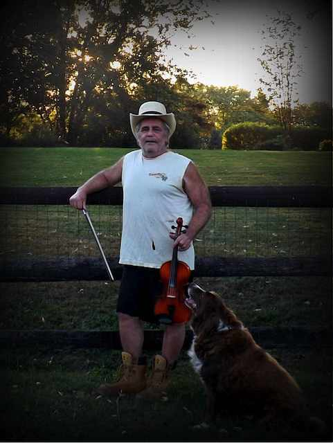 Stondog by the fince with his dog and fiddle.